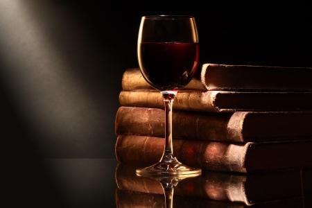 Elegant goblet of red dry wine near old books on dark background