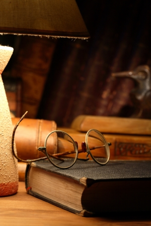 Vintage still life with old spectacles on book near desk lamp Stock Photo - 16747331