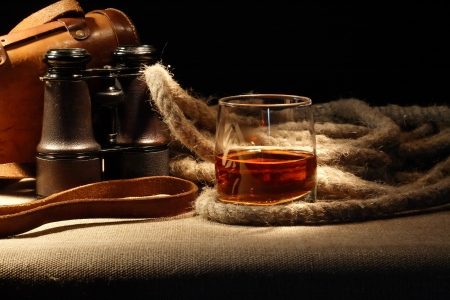 Vintage still life with glass of rum near rope and old binoculars Stock Photo