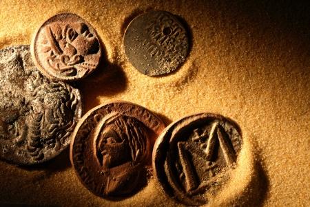 monete antiche: Poche monete antiche su sfondo di sabbia sotto fascio di luce Archivio Fotografico