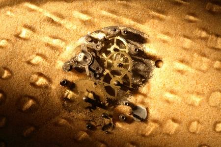 Business concept. Old clock mechanism on sand surface. Nice background photo