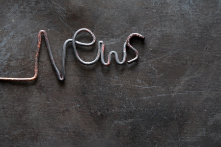 periodical: Periodical Press concept. Word News made from metal wire on grange dark background Stock Photo
