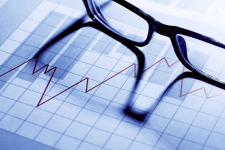 stock trader: Business concept. Spectacles on paper background with chart Stock Photo