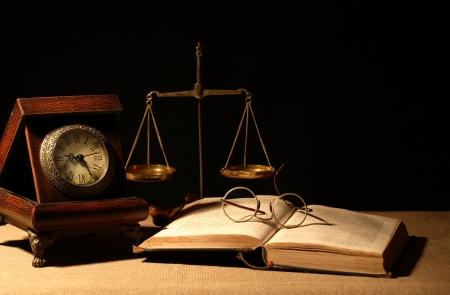 Vintage wooden clock near brass weight scale and book on dark background