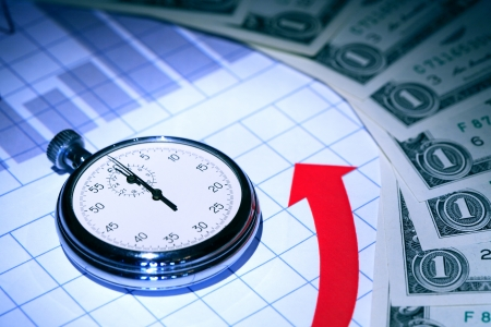 Business concept. Stopwatch on paper background with chart and money photo