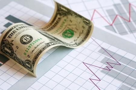 bolsa de valores: Concepto de negocio. Curvado un billete de un dólar en fondo de papel con la carta de negocios