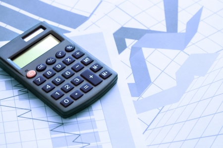 Business concept. Calculator on paper background with business chart photo