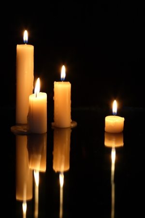 reverberation: Set of lighting candles in a row on dark background with reverberation