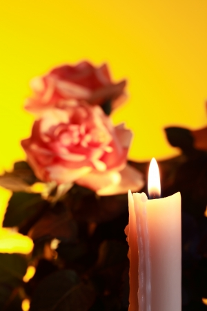 Closeup of lighting candle on yellow background with flowers photo