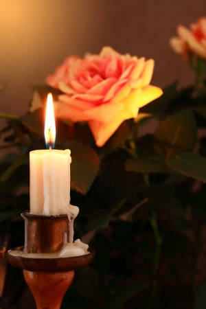 Closeup of lighting candle on dark background with beautiful rose photo