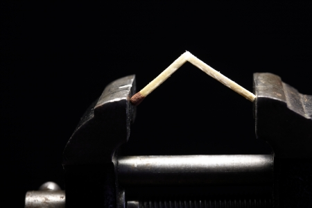 Pressure concept.Cracked match pressured in a bench vice on dark background Stock Photo - 18653064