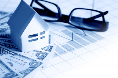 stock trader: Business concept. Paper house near spectacles on one dollar bank notes on paper with chart Stock Photo