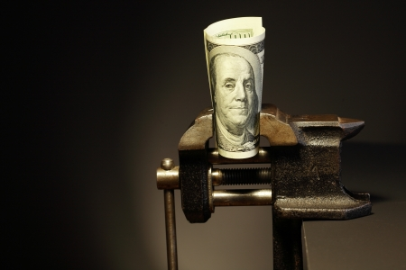 pressured: Economy problem.One hundred dollar bill pressured in a bench vice on dark background Stock Photo