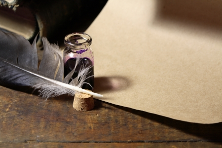 inkpot: Vintage still life with inkpot and feather near scroll and books
