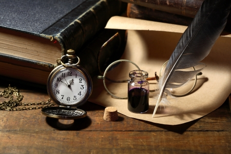 history books: Vintage still life with inkpot and feather near watch and books Stock Photo