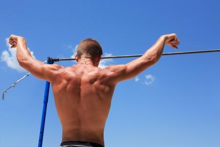 rekstok: Jonge sterke atleet staande voor horizontale balk tegen de blauwe hemel