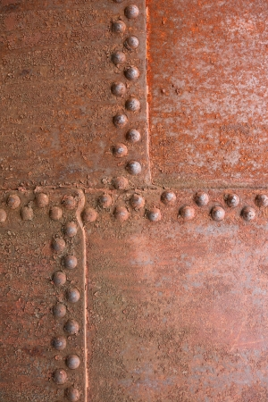 Closeup of old rusty metal background with rivets photo