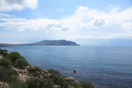 promontory: Summer landscape with big promontory in sea under clouds