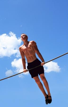 強いの若い選手は鉄棒青い空を背景に運動をしています。