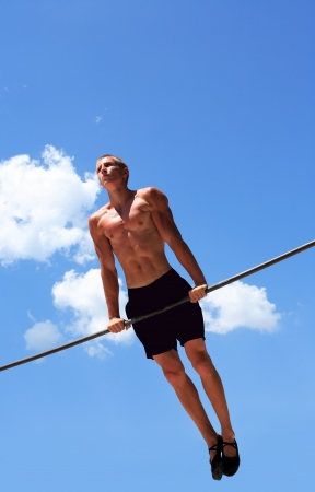 Young strong athlete doing exercise on horizontal bar against blue sky Standard-Bild