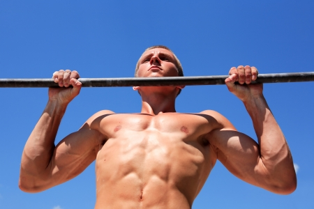 Young strong athlete doing exercise on horizontal bar against blue sky Stock Photo