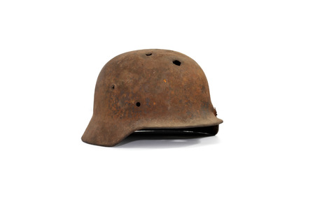 holed: Rusty and holed German military helmet on white background