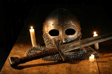medieval warrior: Medieval knight sword and helmet near lighting candles Stock Photo