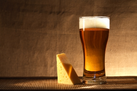 near beer: Glass of freshness beer with foam near cheese on gray canvas background