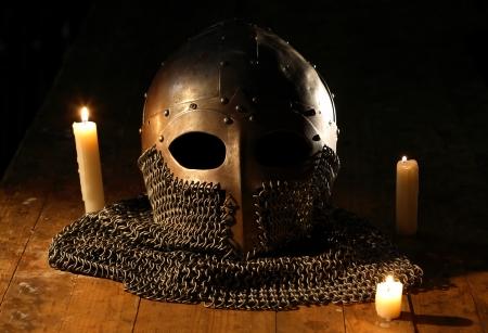 hauberk: Ancient knight helmet with hauberk near candles on wooden background