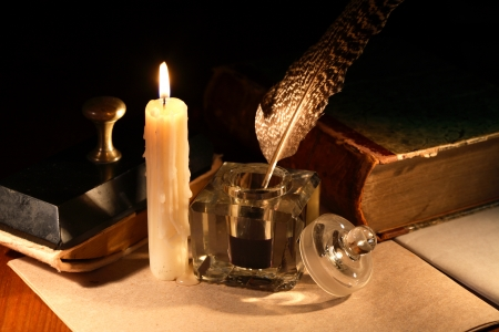 Literature concept. Stylish vintage inkwell near old book and candle on dark background photo