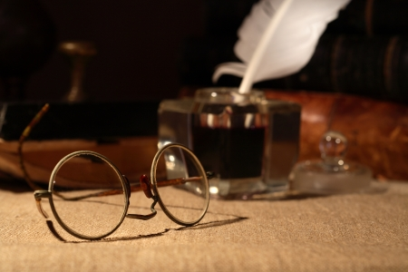 inkstand: Vintage still life. Old spectacles closeup on dark background with inkstand and books