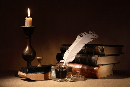 poet: Vintage still life. Old inkstand near lighting candle and books