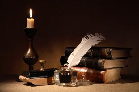 Vintage Stilleben. Old Tintenfass in der Nähe Beleuchtung Kerze und Bücher
