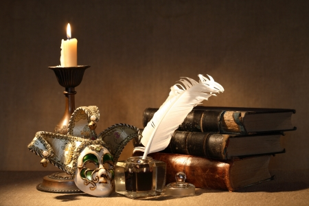 inkstand: Vintage still life. Old inkstand near lighting candle and venetian mask Stock Photo