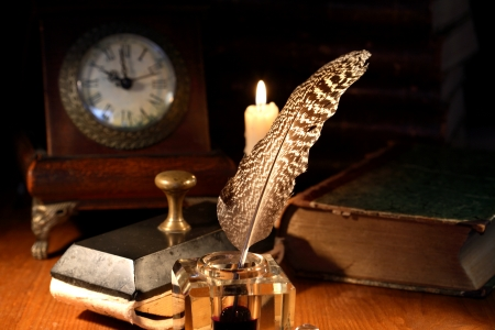 inkstand: Vintage still life. Old inkstand near lighting candle and clock