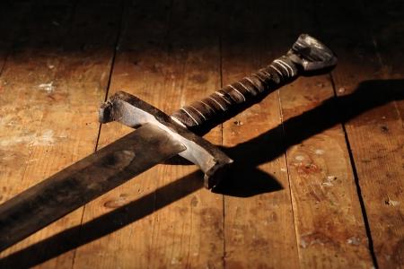 戦争のシンボル。汚れた木製表面に中世の騎士の剣
