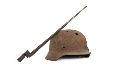 holed: Rusty and holed German military helmet and Russian bayonet on white background Stock Photo