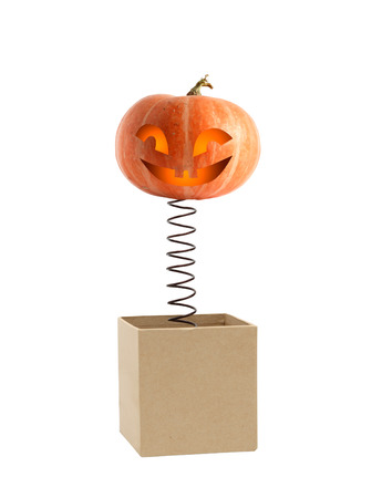 unexpectedness: Smiling pumpkin head on metal spring jumping from box Stock Photo