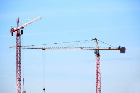 constraction: Pair of constraction cranes against blue sky