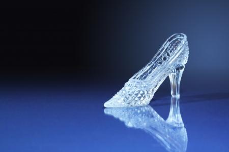 Bella pantofola di vetro su sfondo blu scuro con spazio libero per il testo Archivio Fotografico