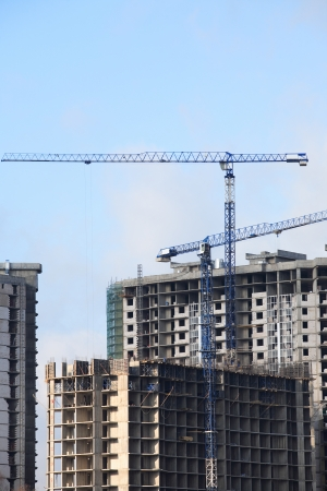 housebuilding: View of house-building with constraction cranes against blue sky Stock Photo