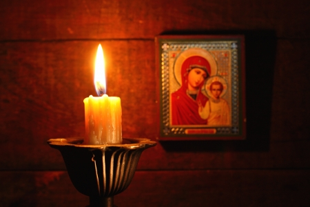 Closeup of lighting candle on wooden background with Christian icon Stock Photo