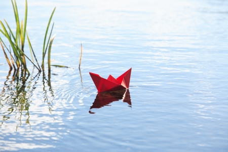 Red paper boat near grass on blue water surface