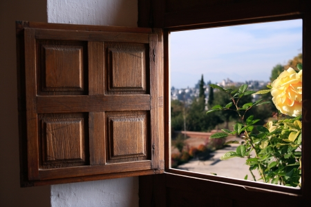 View at summer landscape through old window with wooden shutter photo