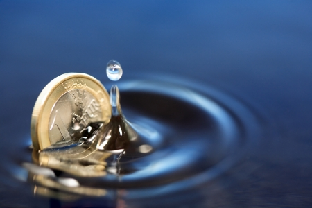 Closeup of one euro coin sinking in water with splash