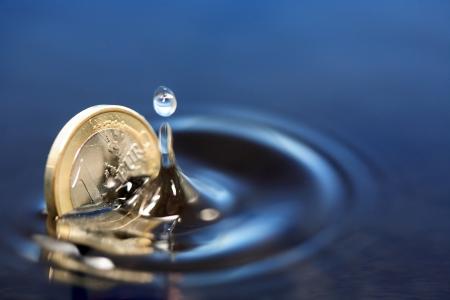 Nahaufnahme von einer Euro-Münze Versenkung in Wasser mit Spritzen Standard-Bild
