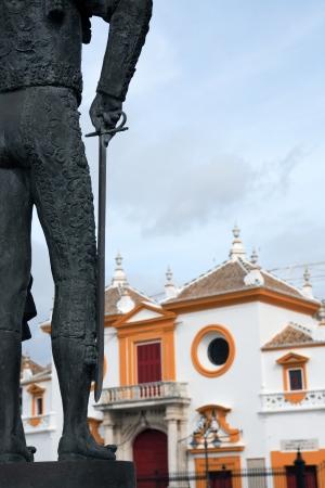 plaza de toros: Fragment of matador statue against famous Seville bullfight arena, Spain Stock Photo
