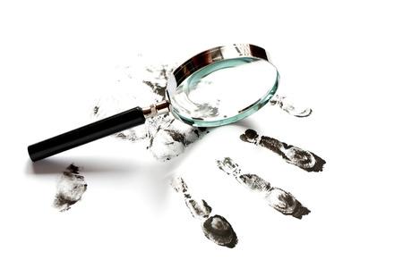 Crime concept. Black fingerprints and magnifying glass on white background photo