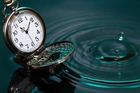 時間の概念。落ちてくるドロップの水にポケット付きヴィンテージ時計