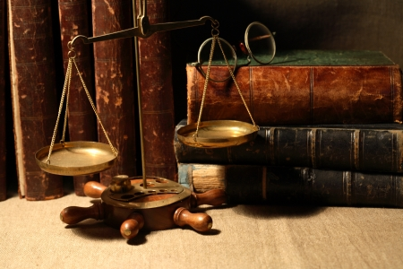 Vintage still life. Old brass weight scale near books and spectacles photo